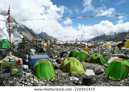 Colorful tents and Tibetan prayer flags at Everest Base Camp, Khumbu Region, Nepal. - stock photo
