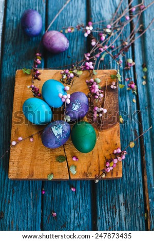 Colorful Textured Easter Eggs with spring shoots and vintage flowers taken on old aged scored blue wooden surface. Rustic style  - stock photo