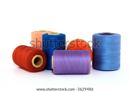 Colorful thread bobbins, isolated on white background.