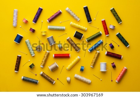 Colorful thread spools disorganized over bright yellow background, above view - stock photo