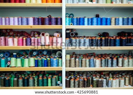 Colorful thread spools in fabric industry - stock photo
