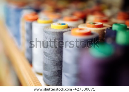 Colorful thread spools used in fabric and textile industry - stock photo