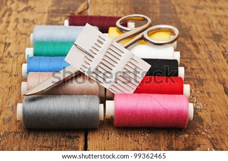 Colorful threads and old scissors on the old wooden table