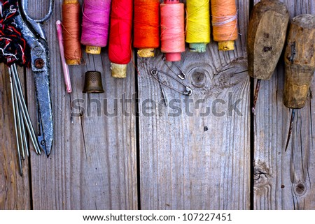 Colorful threads and old scissors on the old wooden table/Old sewing accessories - stock photo