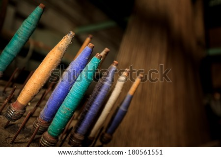 Colorful threads in an old spinnery - stock photo