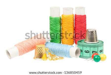 Colorful threads with sewing accessories isolated on white background cut-out - stock photo
