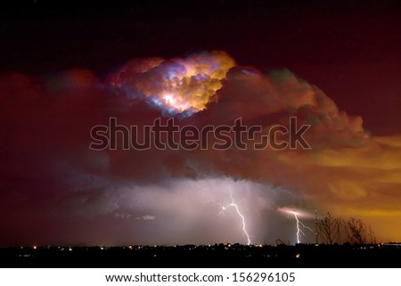 Colorful thunderstorm thunderhead lit up with lightning bolts striking in Boulder County Colorado.  - stock photo