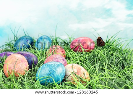 Colorful tie dyed Easter eggs in the grass. Extreme shallow DOF. - stock photo
