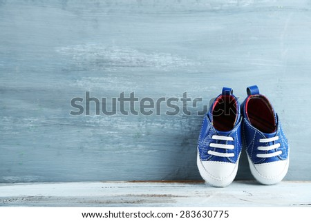 Colorful toddler shoes on wooden background - stock photo