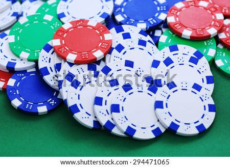 Colorful tokens in casino on green background