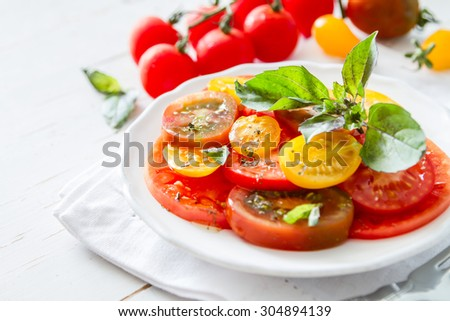 Colorful tomato salad basil white plate on rustic wood background