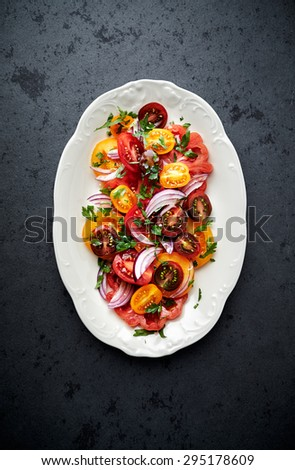 Colorful tomato salad with fresh parsley - stock photo