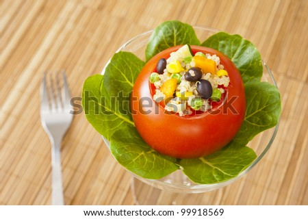 Colorful Tomato stuffed with quinoa salad of black beans and vegetables - stock photo