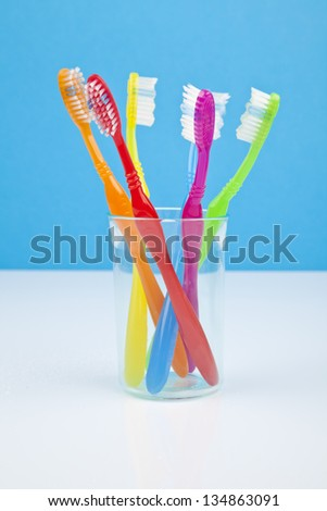 colorful toothbrushes in a water glass - stock photo