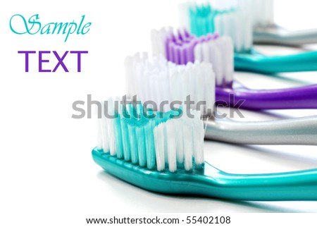 Colorful toothbrushes on white background with copy space.  Macro with shallow dof. - stock photo