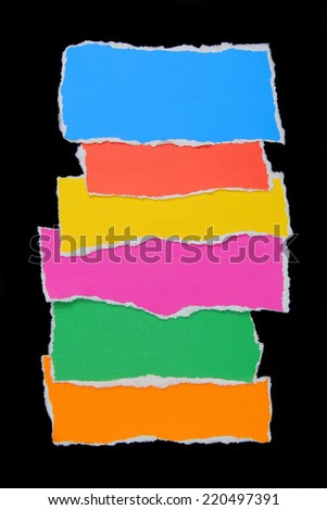 colorful torn paper on black paper background - stock photo