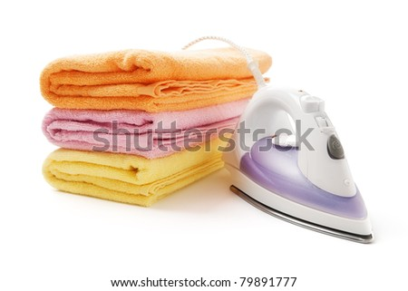 Colorful towels and electric iron - stock photo