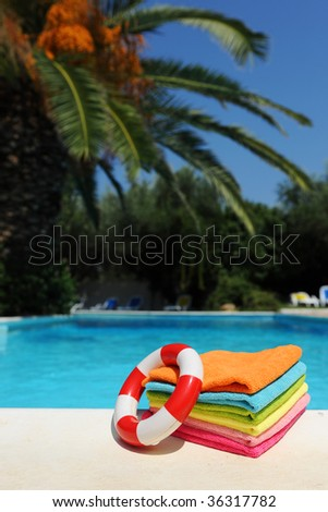 colorful towels and life buoy near the tropical swimmig pool - stock photo