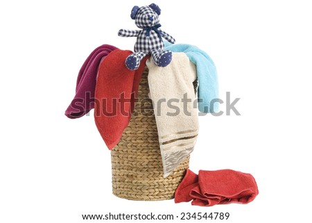 colorful towels in a basket isolated on white background and a resting teddy bear - stock photo