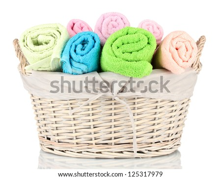 Colorful towels in basket isolated on white - stock photo