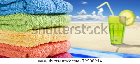 Colorful towels on a white with a cold drink - stock photo