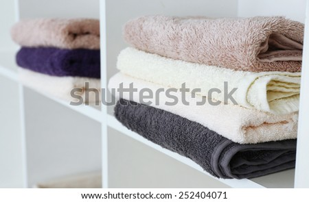 Colorful towels on shelf of rack background - stock photo