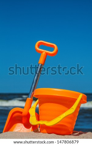 Colorful toy set on the sunny beach - stock photo