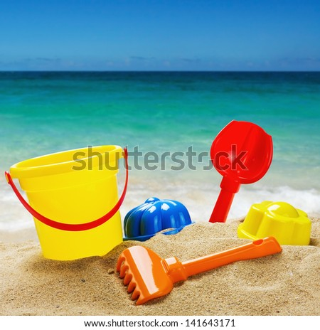 colorful toys for childrens sandboxes against the sea and the beach - stock photo