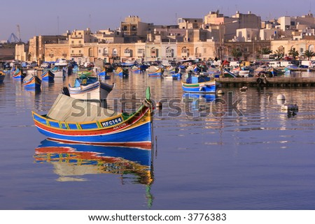 Colorful, traditional fishing boats against the backdrop of Marsaxlokk village in the mediterranean island of Malta. See portfolio for more. - stock photo