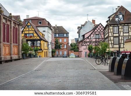 Colorful traditional french houses and empty road in Colmar, Alsace region, France. - stock photo
