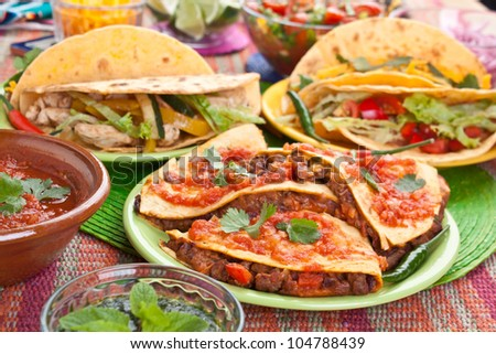 Colorful Traditional Mexican food dishes: various fajitas, quesadillas, salsa verde, tomato salsa, salsa cruda served on a beautifully decorated table - stock photo
