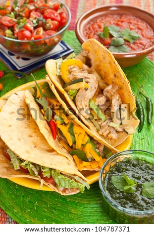 Colorful Traditional Mexican food dishes: various fajitas, salsa verde, tomato salsa, salsa cruda served on a beautifully decorated table - stock photo