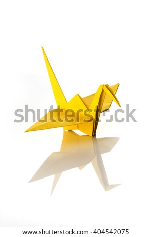 Colorful traditional origami bird (crane) made from yellow paper isolated on white background - stock photo