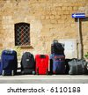 Colorful travel bags all lined up outside a boutique hotel - stock photo