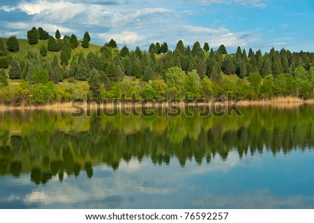 Colorful Trees in spring reflected on the water surface - stock photo