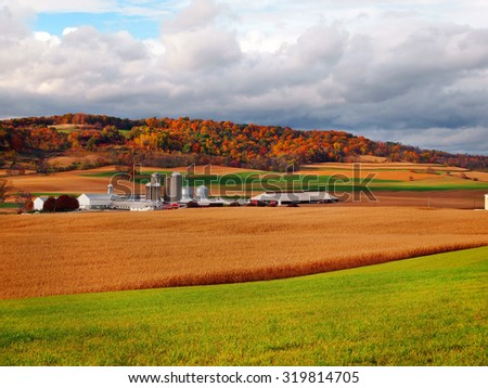 Colorful trees, turned orange, red, and yellow in October, stand behind and amongst the rolling hills of a farm in the countryside.  - stock photo