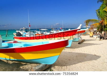 colorful tropical boats beached in the sand Isla Mujeres Mexico - stock photo