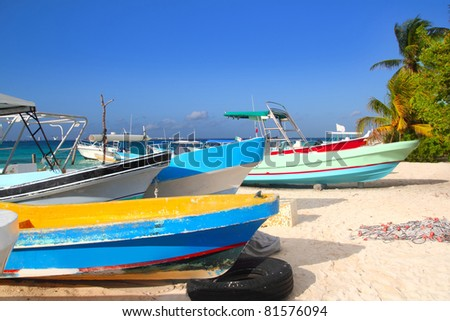 colorful tropical boats beached in the sand of Isla Mujeres Mexico - stock photo