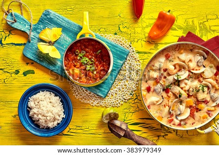 Colorful tropical Brazilian seafood casserole with Venus shell clams in a savory spicy stew served with a bowl of rice and spicy chili dip on a vivid yellow rustic table - stock photo