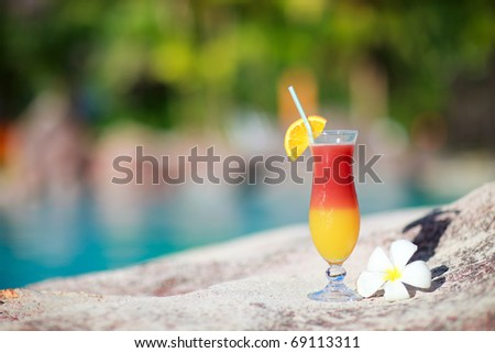 Colorful tropical cocktail and frangipani flower near water - stock photo