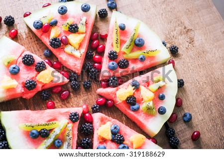 colorful tropical fruit watermelon pizza topped with kiwifruit, blueberries, orange and fresh berries cut into segments on a rustic wooden board - stock photo