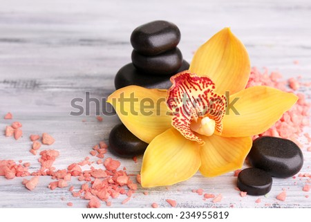 Colorful tropical orchid flowers and spa stones on color wooden background - stock photo