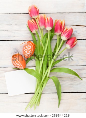 Colorful tulip bouquet, easter eggs and blank greeting card. Top view over white wooden table - stock photo