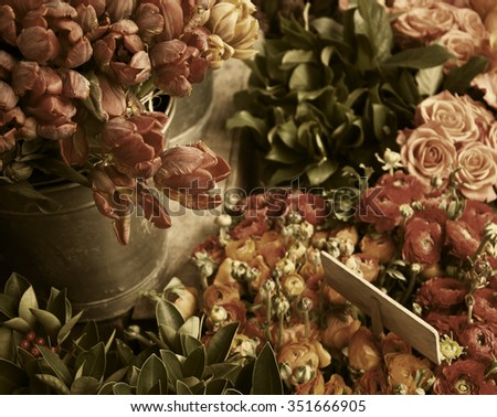 Colorful tulips and buttercups flowers with wooden price tag. Selective focus. Aged photo. - stock photo