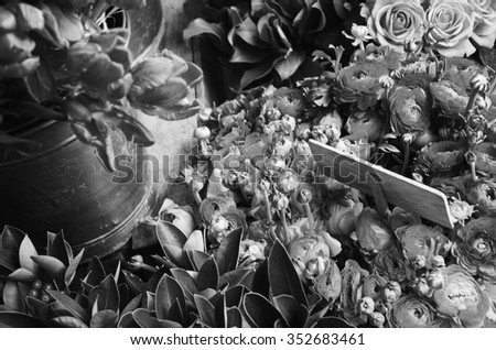 Colorful tulips and buttercups flowers with wooden price tag. Selective focus on buttercup flowers. Aged photo. Black and white. - stock photo