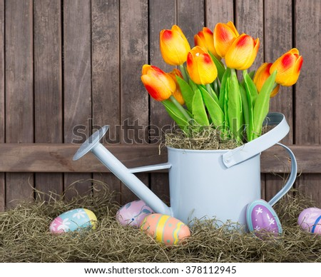 Colorful tulips and Easter eggs on a wood background