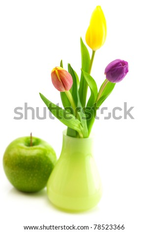 colorful tulips in vase and apple isolated on white