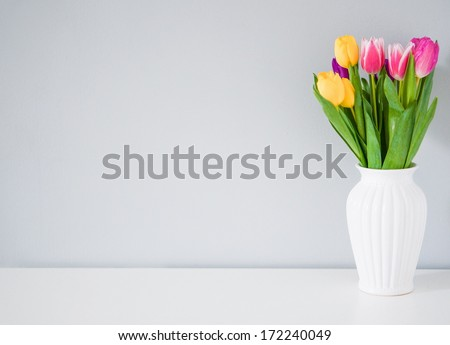 Colorful tulips in white vase on the table on light grey background - stock photo