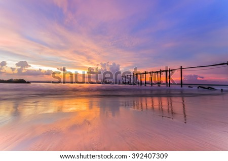 Colorful twilight and reflection on sand and old moldy bridge.
