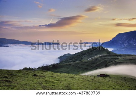Colorful twilight morning mist up the hills in the Romania Apuseni Carpathian Mountains  - stock photo